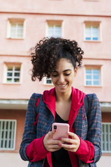 Portrait of happy young woman using mobile phone - ERRF02037