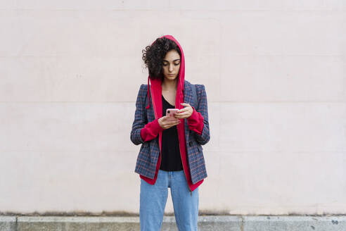 Portrait of young woman using mobile phone outdoors - ERRF02040
