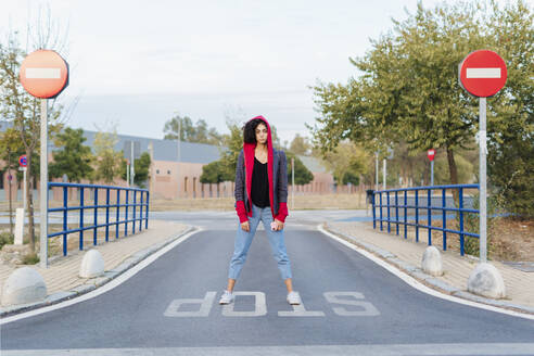 Portrait of young woman with mobile phone standing on the word 'stop' on the street - ERRF02043