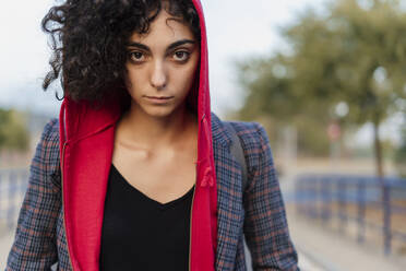 Portrait of young woman with curly hair wearing hooded jacket - ERRF02049