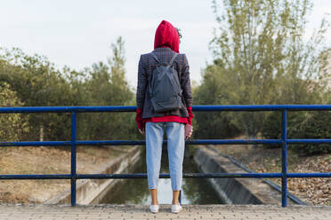 Back view of young woman with backpack and mobile phone standing on a bridge - ERRF02052