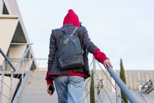 Back view of young woman with backpack and mobile phone wearing red hooded jacket walking upstairs - ERRF02055