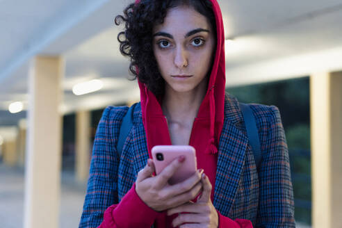 Portrait of young woman with mobile phone in the evening - ERRF02061
