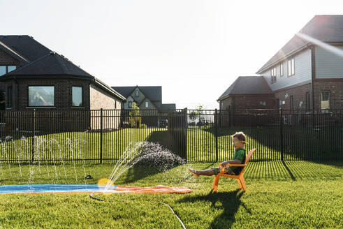 Boy in swimming goggles sitting on chair at backyard against clear sky - CAVF69245