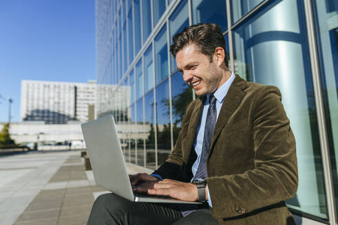 Happy businessman sitting in urban business district using laptop, Madrid, Spain - KIJF02732