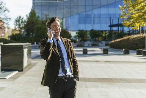 Laughing businessman on the phone in urban business district, Madrid, Spain - KIJF02735