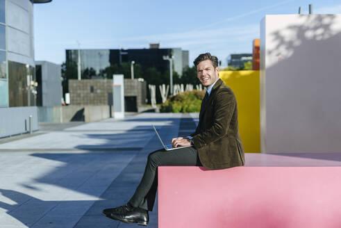 Businessman sitting in urban business district using laptop, Madrid, Spain - KIJF02738