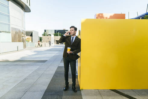 Businessman on the phone in urban business district, Madrid, Spain - KIJF02747