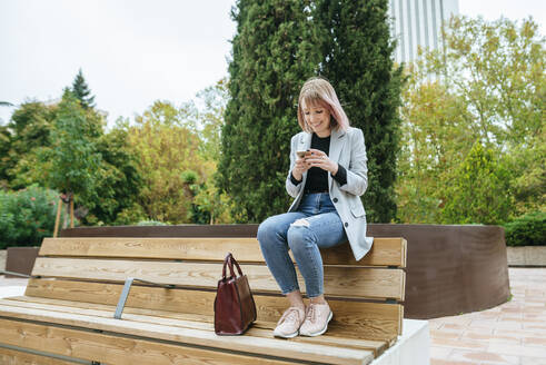 Smiling woman sitting on park bench using cell phone - KIJF02795