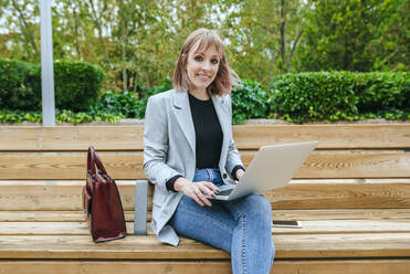 Smiling woman sitting on park bench using laptop - KIJF02798