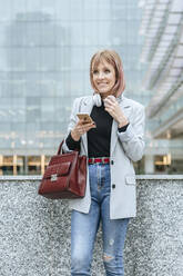 Smiling woman with cell phone in the city - KIJF02801