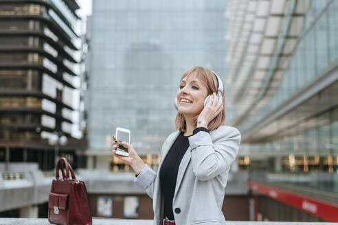 Happy woman listening to music with headphones in the city - KIJF02804