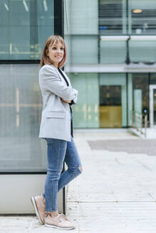 Smiling busineswoman leaning against glass building - KIJF02816