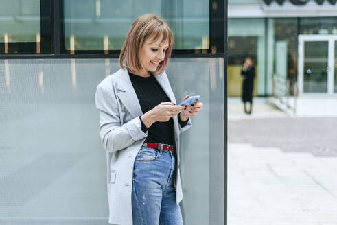Smiling woman using cell phone at glass building - KIJF02819