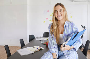 Portait of smiling casual young businesswoman in an office - IGGF01452