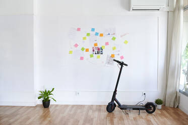Electric scooter in front of a wall full of sticky notes in a bright modern office - IGGF01458