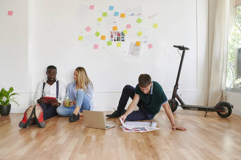 Young business people sitting together in an office having a meeting - IGGF01461