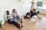 Happy young business people sitting together in an office having an informal meeting - IGGF01464