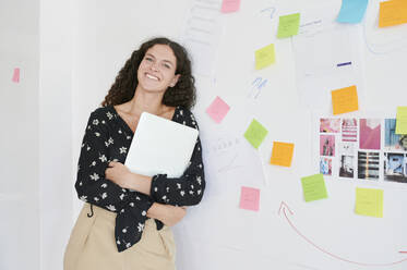 Portait of smiling young businesswoman leaning against a wall full of sticky notes in an office - IGGF01467