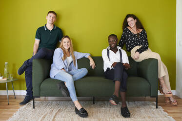 Portrait of smiling casual colleagues sitting on a sofa in a green walled office lounge - IGGF01479