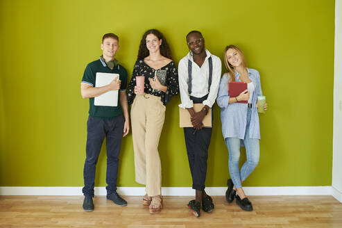 Portrait of smiling casual colleagues standing together in front of a green wall in a modern office - IGGF01485