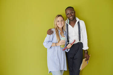 Portrait of smiling casual business couple standing together in front of a green wall - IGGF01488