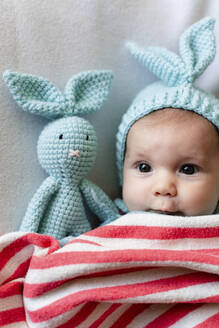 Baby girl with bunny hat and a bunny toy on bed with a blanket - GEMF03304