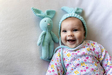 Baby girl with bunny hat and a bunny toy lying on bed - GEMF03307