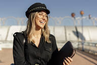 Young blond laughing businesswoman wearing black sailor's cap and holding laptop bag - ERRF02074