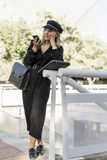 Young blond businesswoman wearing black hat and using smartphone - ERRF02080