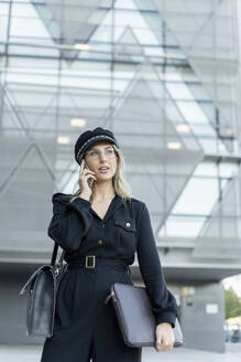 Young blond businesswoman wearing black sailor's cap, holding laptop bag and using smartphone - ERRF02086