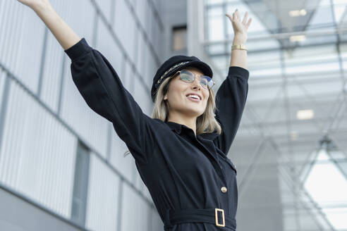 Young blond businesswoman wearing black sailor's cap and raising arms - ERRF02092