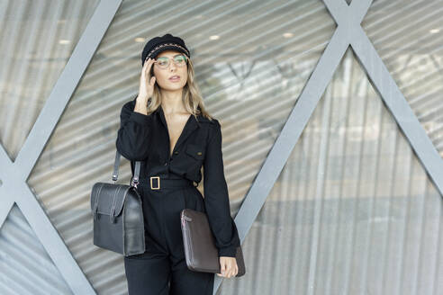 Young blond businesswoman wearing black hat and holding laptop bag, looking sideways - ERRF02095