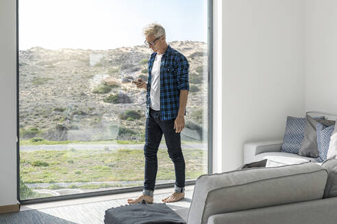 Casual businessman in front of window in modern home holding smartphone - SBOF02040