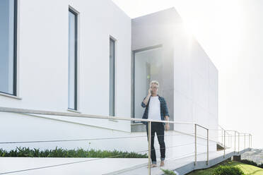 Casual man outside his modern home talking on the phone - SBOF02046
