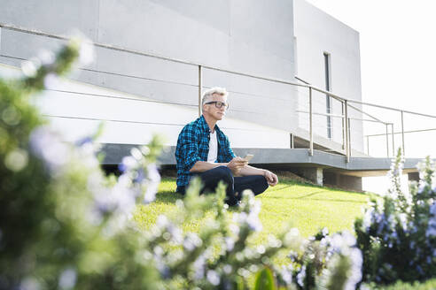 Casual man outside his modern home holding smartphone - SBOF02049