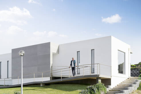 Casual man standing in front of his modern home - SBOF02052