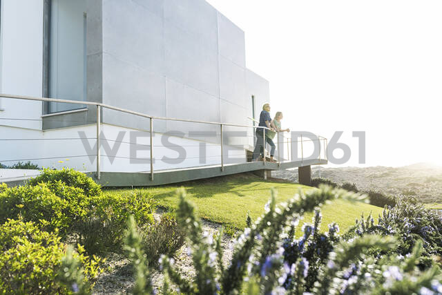 Couple standing in front of their modern home looking around - SBOF02058 - Steve Brookland/Westend61