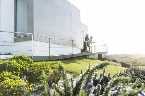 Couple standing in front of their modern home looking around - SBOF02058