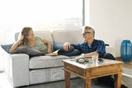 couple smiling at each other on couch at modern home - SBOF02061