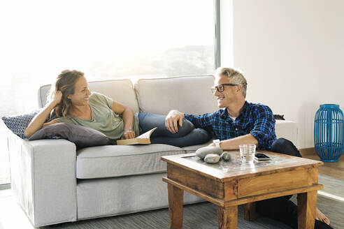 Couple smiling at each other on couch in modern home - SBOF02061