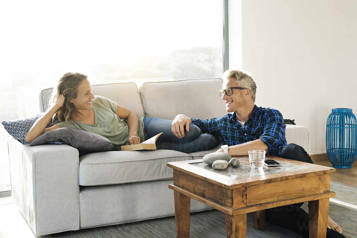 Couple smiling at each other on couch in modern home - SBOF02061 - Steve Brookland/Westend61