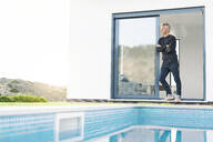 Smart man standing in front of his modern home with pool looking at the landscape - SBOF02067