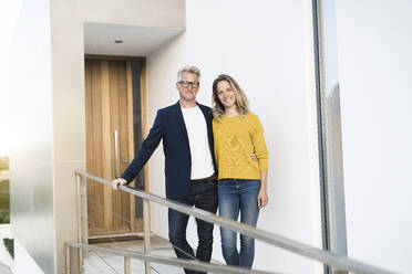 Portrait of smiling couple standing in front of their modern home - SBOF02073