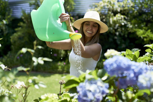 Woman watering the plants in the garden, Pretoria, South Africa - VEGF00803