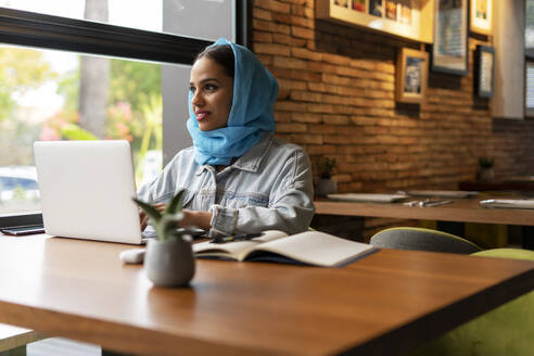 Businesswoman wearing turquoise hijab in a cafe and working, using laptop - ERRF02104