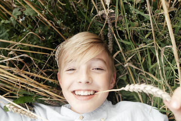 Portrait of smiling blond boy with oat ear in mouth lying in an oat field - EYAF00691