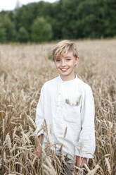 Portrait of happy blond boy standing in an oat field - EYAF00697
