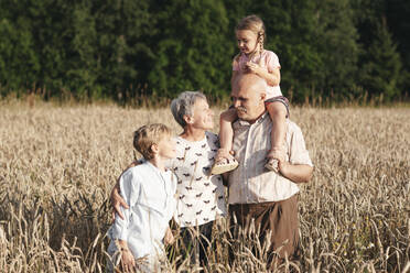 Family portrait of grandparents with their grandchildren in an oat field - EYAF00700