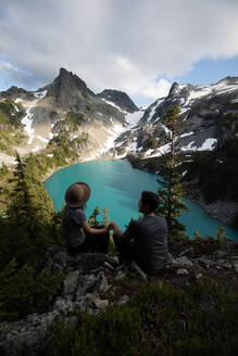 Couple enjoying scenic view, Alpine Blue Lake, Washington, USA - ISF22707